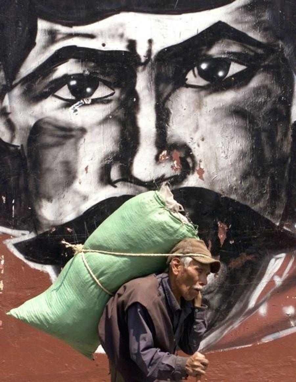 En mars 2001, un vieil homme marche devant une représentation d'Emiliano Zapata à Mexico.