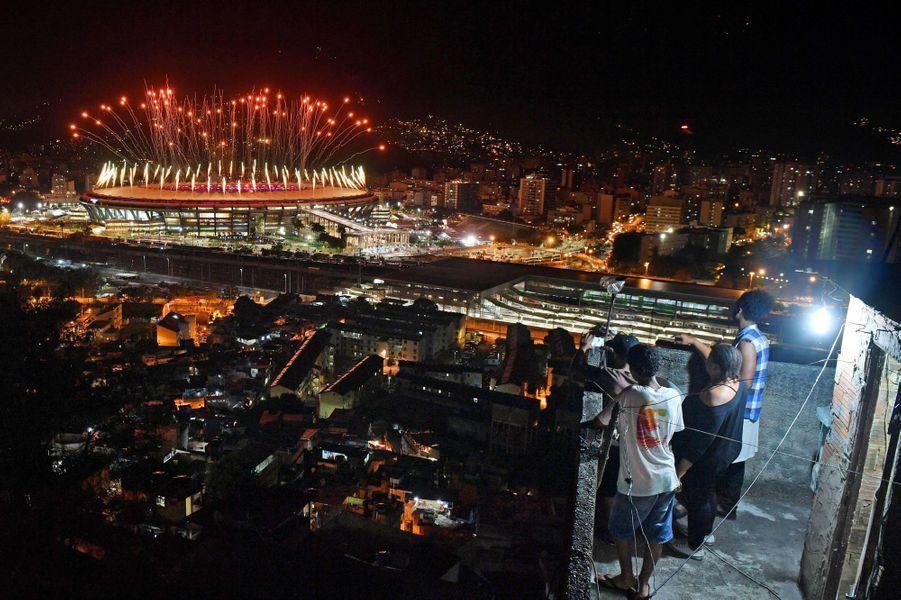 Des Brésiliens regardent le stade de Maracana s'illuminer pour l'ouverture des Jeux Olympiques de Rio, le 5 août 2016.