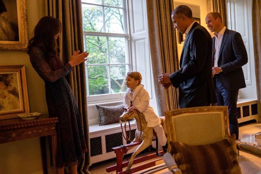 Le prince George fait du cheval à bascule à Kensington Palace devant ses parents et le président des Etats-Unis Barack Obama, le 22 avril 2016.