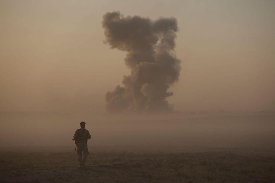 Près de Naweran, le 20 octobre 2016, en Irak : un peshmerga observe le panache de fumée provoqué par une frappe aérienne de la coalition, peu avant la tombée de la nuit.