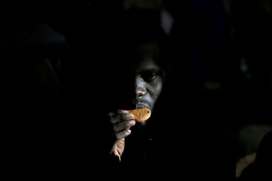 Un migrant mange un biscuit donné par le Migrant Offshore Aid Station (MOAS) qui la repêchait en mer, au large de la Libye.