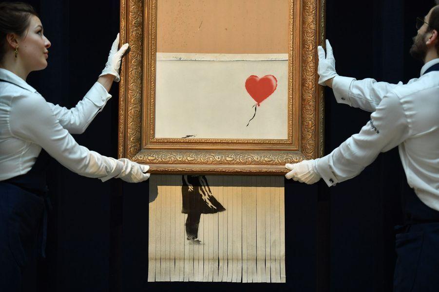"""La maison de vente Sotheby's Londres expose """"Girl with Balloon"""", le tableau partiellement autodetruit de l'artiste Banksy, qui a été renommé """"Love is in the bin""""."""