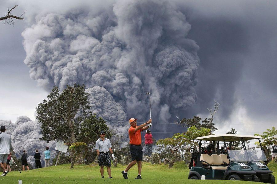 Hawaii, Etats-Unis, 15 mai 2018? Des joueurs de golf continuant de jouer alors que l'alerte rouge a été déclenché dans le Parc national des volcans de Hawaii. L'éruption du volcan Kilauea, qui émet un gigantesque panache de fumée, est imminente.