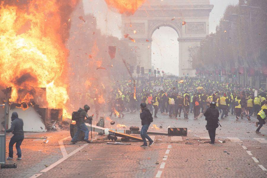 """Les """"gilets jaunes"""" sont venus de toute la France pour manifester à Paris le 24 novembre 2018 mais soudain, sur les Champs-Elysées, tout a dérapé et s'est transformé en mini-émeute : explosion d'une bouteille de gaz sur une barricade. La police éloigne les """"gilets jaunes"""" à l'arrière de la manifestation, l'Arc-de-Triomphe en arrière-plan."""