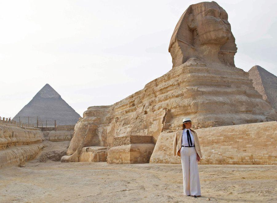 Melania Trump, l'épouse du président américain, a effectué du 3 au 6 octobre 2018 une tournée diplomatique et humanitaire en Afrique. En Egypte, vêtue d'un pantalon Valentino, veste Ralph Lauren, ballerines et chapeau Chanel elle admire la beauté du site de Gizeh. Derrière elle, le Sphinx.