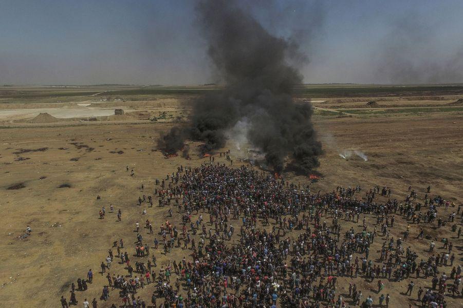 """Gaza, 14 mai 2018. 59 Palestiniens ont été tués et plus de 2 400 blessés par l'armée israélienne à la frontière entre Gaza et Israël, le jour de l'inauguration de la nouvelle ambassade des Etats-Unis à Jérusalem et des fêtes du 70e anniversaire de la création de l'Etat hébreu. De leur côté, Les Palestiniens commémoraient la Nakba (en arabe, la """"catastrophe"""" de l'exode de 1948). Vue générale de la foule des civils palestiniens face aux positions de Tsahal, de l'autre côté de la frontière. Seule protection des manifestants, la fumée des pneus incendiés."""