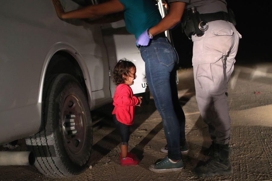 12 juin 2018. Une fille de deux ans native du Honduras pleure alors que sa mère est fouillée à la frontière entre les Etats-Unis et le Mexique.