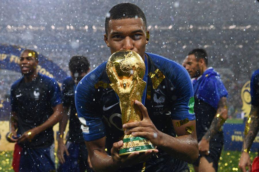 Kylian Mbappe, le jeune attaquant de l'équipe de France, embrasse la Coupe du Monde après la victoire des Bleus.