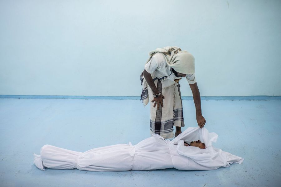 Le corps d'un combattant yémeni mort à Hodeidah est veillé par un ami à la morgue d'un hôpital de campagne, le 22 septembre à Al Khawkhah.
