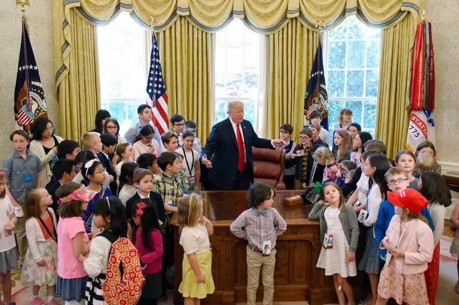 Donald Trump dans le Bureau ovale, entouré d'enfants de journalistes et des employés de la Maison-Blanche, le 26 avril 2018.
