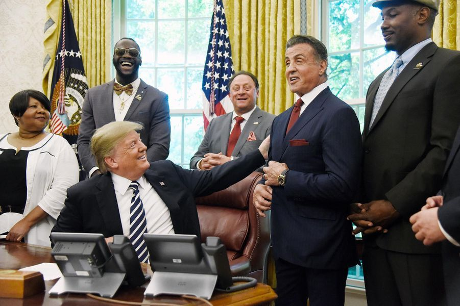 Donald Trump salue Sylvester Stallone dans le Bureau ovale le 24 mai 2018, après avoir signé l'acte réhabilitant à titre posthume le boxeur Jack Johnson,condamné à la prison pour des motifs racistes.