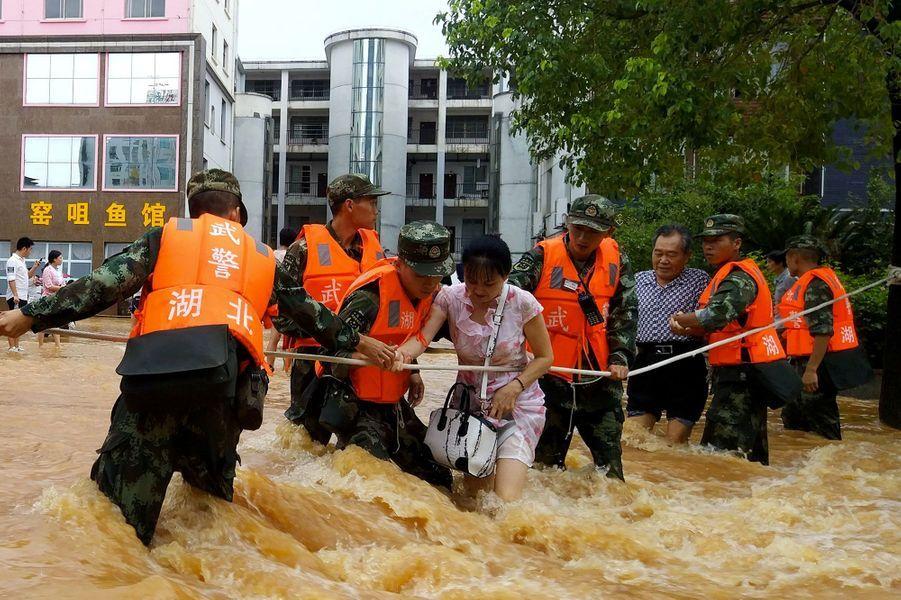 Des sauveteurs évacuent une dame, dans la province de Hubei, en Chine.