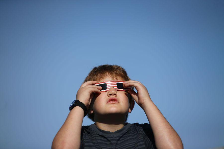 Un petit garçon prend soin de mettre ses lunettes de protection pour admirer l'éclipse à Depoe Bay, dans l'Oregon, une des premières villes sur le trajet de l'éclipse.
