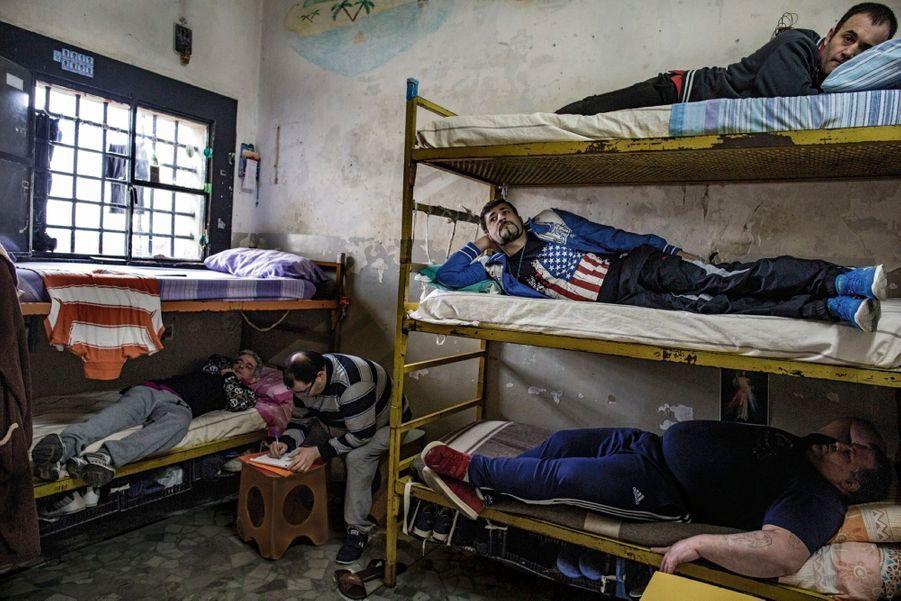 L'un écrit à sa famille, les autres tentent une sieste, l'« activité » la plus courante en prison. Au centre de Poggioreale, à Naples.