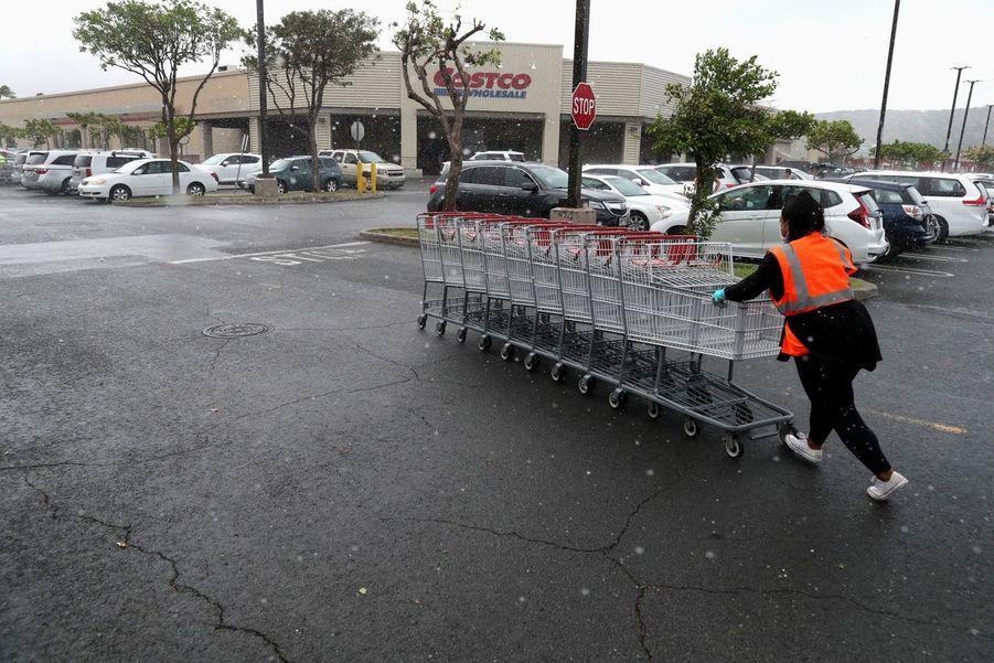 Une employée d'un supermarché d'Hawaï prépare le magasin à l'arrivée de l'ouragan Douglas.