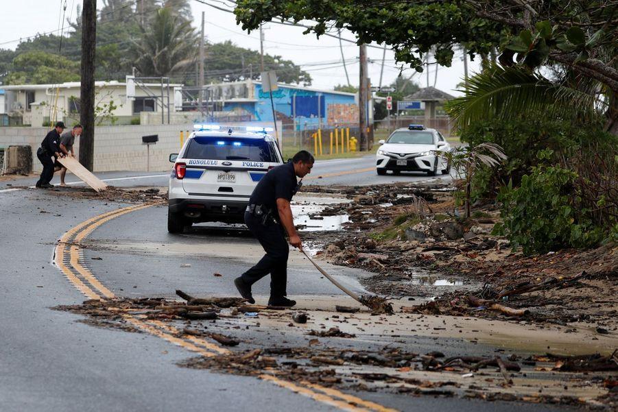 Un policier nettoie une route inondée à Hawaï.