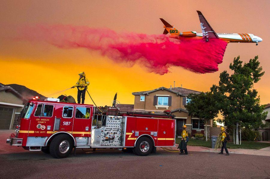 Un avion largue un cocktail ignifuge à Lake Elsinore, en Californie, le 8 août, tandis que les pompiers tentent de contenir le feu qui s'approche des maisons.