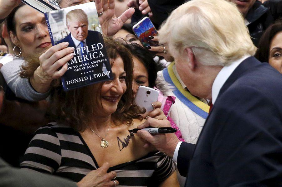 Donald Trump signe un autographe sur la poitrine d'une de ses supportrices àManassas, le 2 décembre 2015.