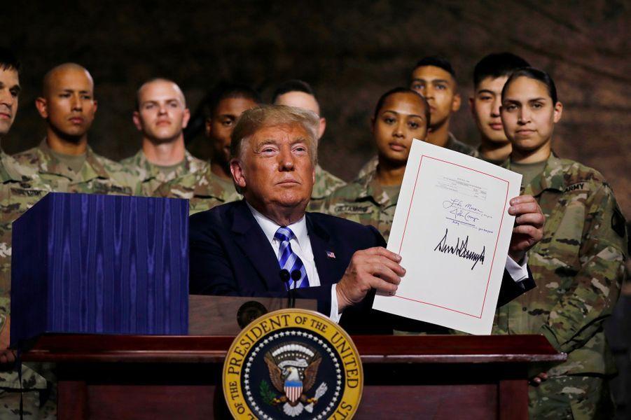 Donald Trump brandit sa signature sur la loi de finances des forces armées, lundi à Fort Drum.