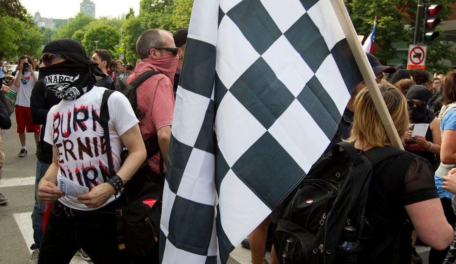 """Un manifestant porte un tee-shirt sur lequel il est écrit """"Brûle Bernie Brûle"""". Il s'attaque à Bernie Ecclestone, le patron de la Formule 1."""