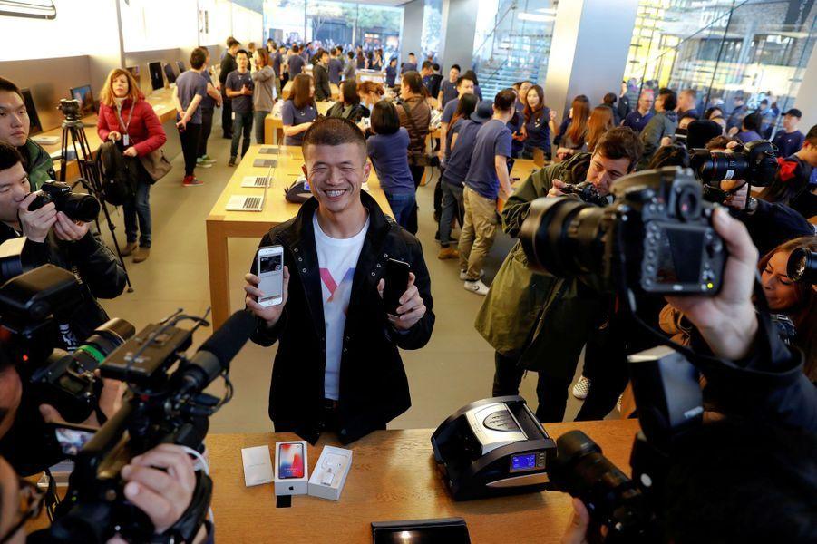 Le premier client a avoir obtenu un iPhone X montre son nouveau jouet, dans un Apple Store de Pékin, en Chine.