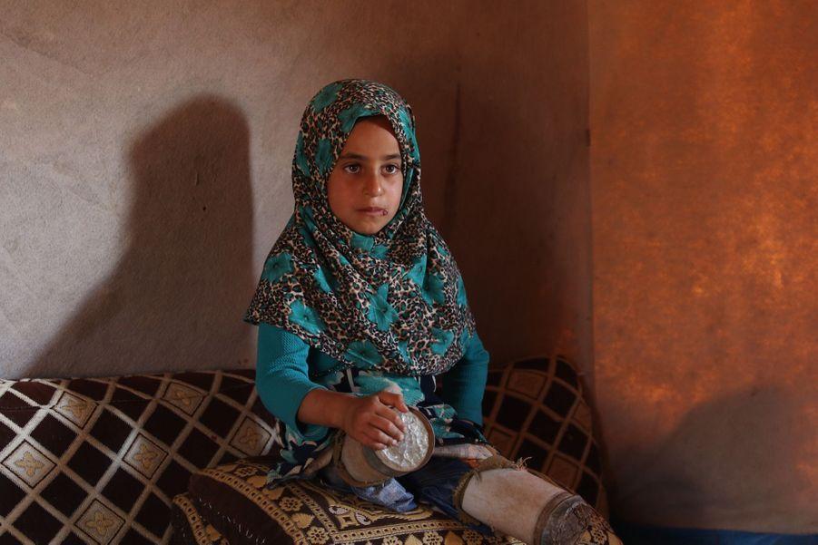 La petite Syrienne née sans jambes, Maya, avec les boîtes de conserve lui servant de prothèses, le 20 juin 2018 au camp de Serjilla, un camp de déplacés du nord-ouest de la Syrie.
