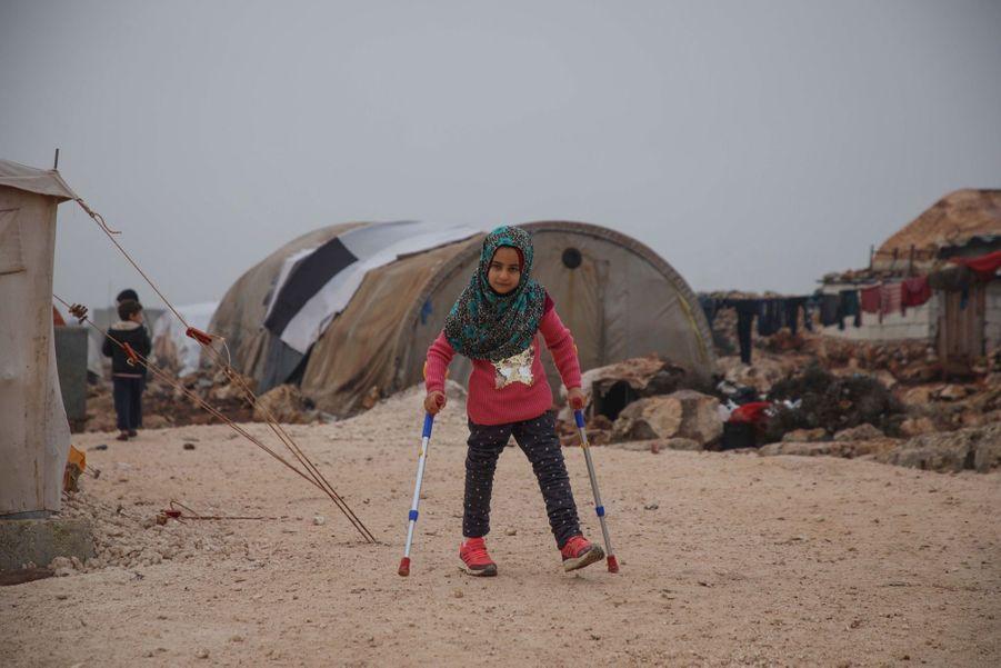 La petite Syrienne née sans jambes, Maya, troque des boîtes de conserve pour des prothèses, le 9 décembre 2018 au camp de Serjilla, un camp de déplacés du nord-ouest de la Syrie.