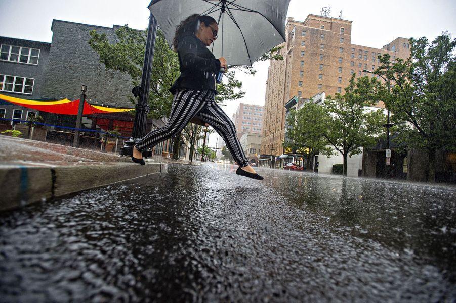 Une femme enjambe l'eau surHamilton Street à Allentown en Pennsylvanie.