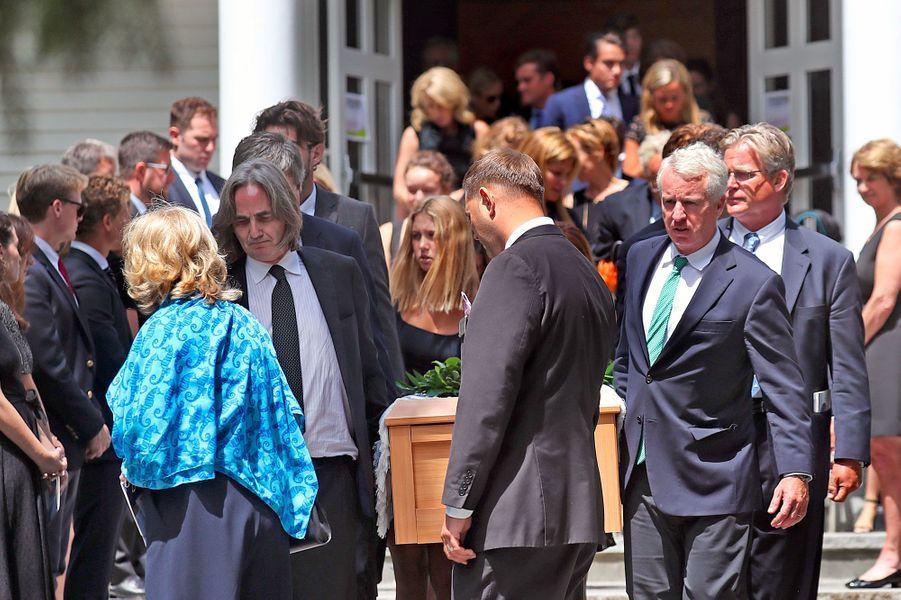 Courtney Kennedy Hill, en bleu, devant Paul Michael Hill, alors qu'il porte le cercueil de leur fille, lundi à Centerville.