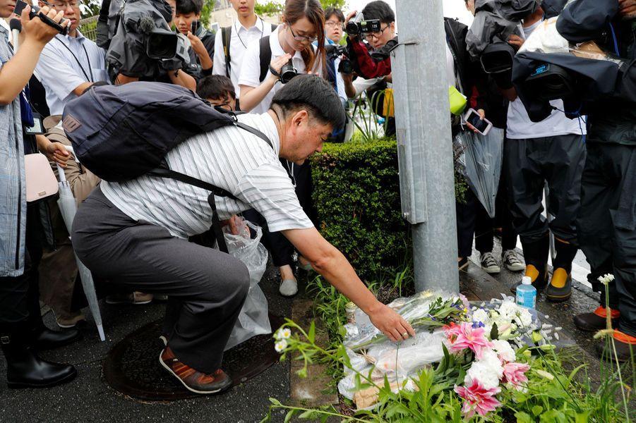 Des personnes déposent des fleurs devant le studio d'animation Kyoto