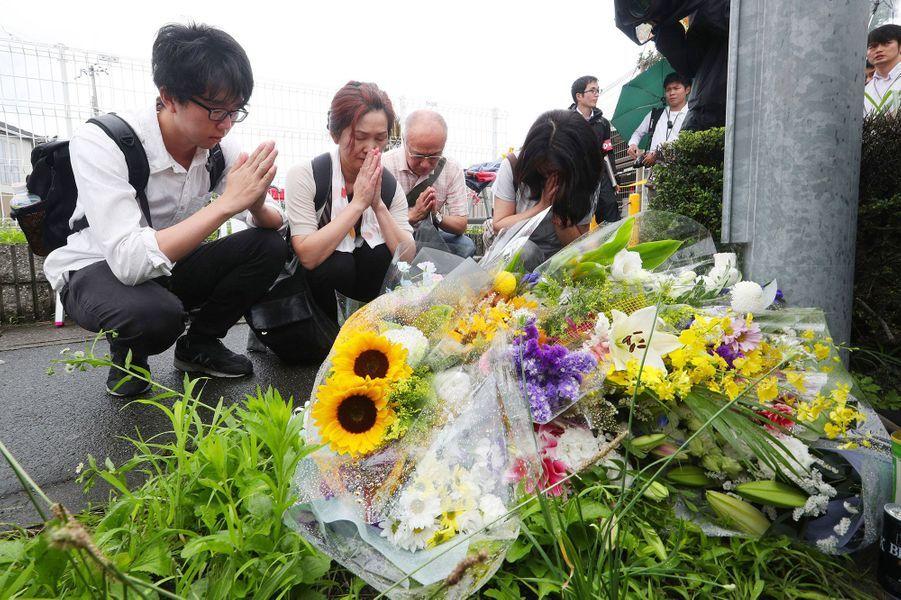 Des personnes prient pour les victimes de l'incendie du studio Kyoto Animation