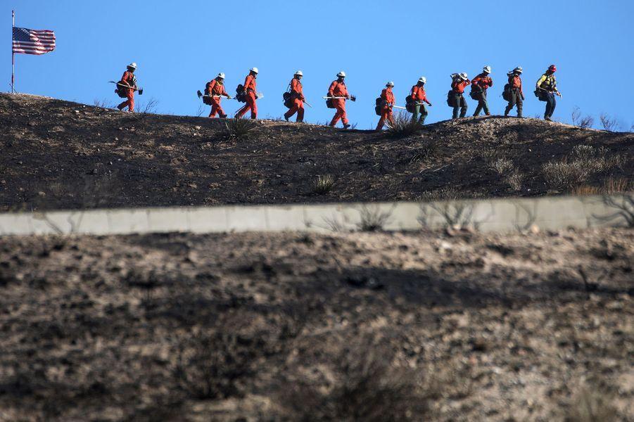 Des pompiers travaillent à éteindre les points chauds du Tick Fire le 25 octobre 2019 à Canyon Country