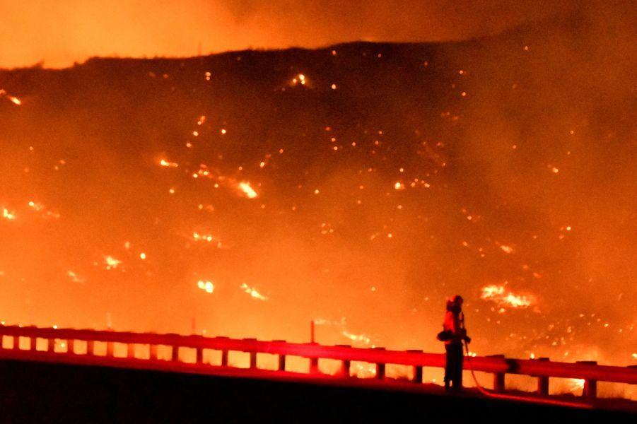 Les pompiers combattent un incendie alors qu'un feu de forêt poussé par le vent continue de brûler dans Canyon Country au nord de Los Angeles, Californie, le 25 octobre 2019
