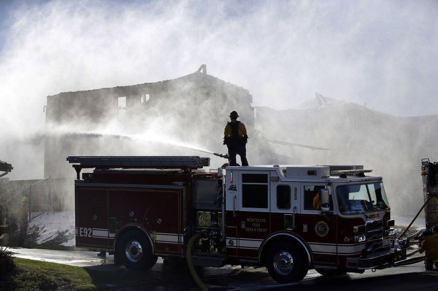 Un pompier tente d'éteindre un incendie de résidence provoqué par un feu de forêt depuis un camion de pompiers vendredi 25 octobre 2019 à Santa Clarita