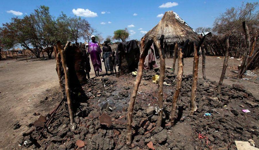Une famille se tient à côté d'un abri brûlé par des rebelles lors d'affrontements ethniques en avril. En janvier, Pibor avait déjà été le théâtre de violences. Des jeunes de la tribu des Lou Nuers'en étaient pris à la ville en incendiant des huttes et en pillant l'hôpital de Médecins sans frontières. Un bataillon de 700 casques bleus kenyans avait été déployé. L'ONU avait alors redouté une crise humanitaire.