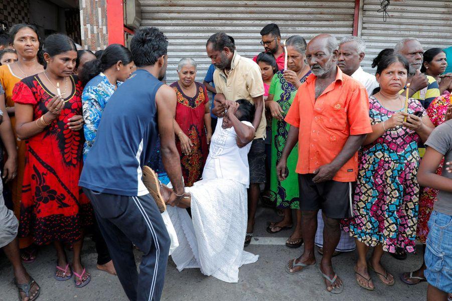 A Colombo, mardi, pendant les minutes de silence, une femme s'est effondrée, avant d'être aidée.