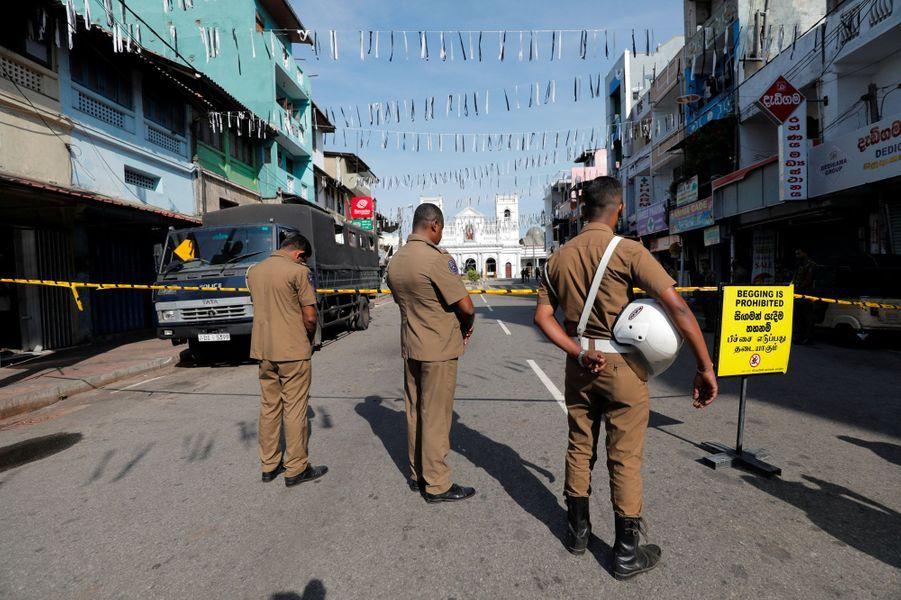 Des membres des forces de sécurités se recueillent durant trois minutes de silence, près de l'église Saint-Antoine, à Colombo, mardi.