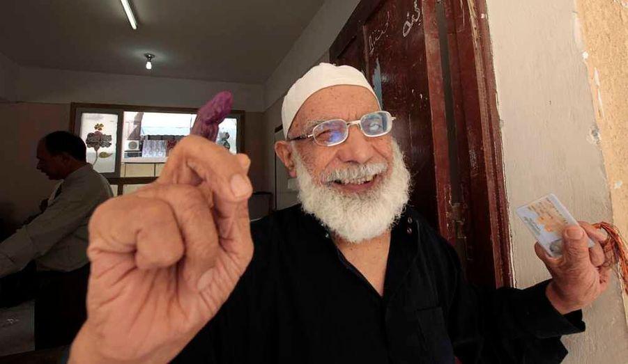 Un homme montrant fièrement son doigt trempé dans l'encre