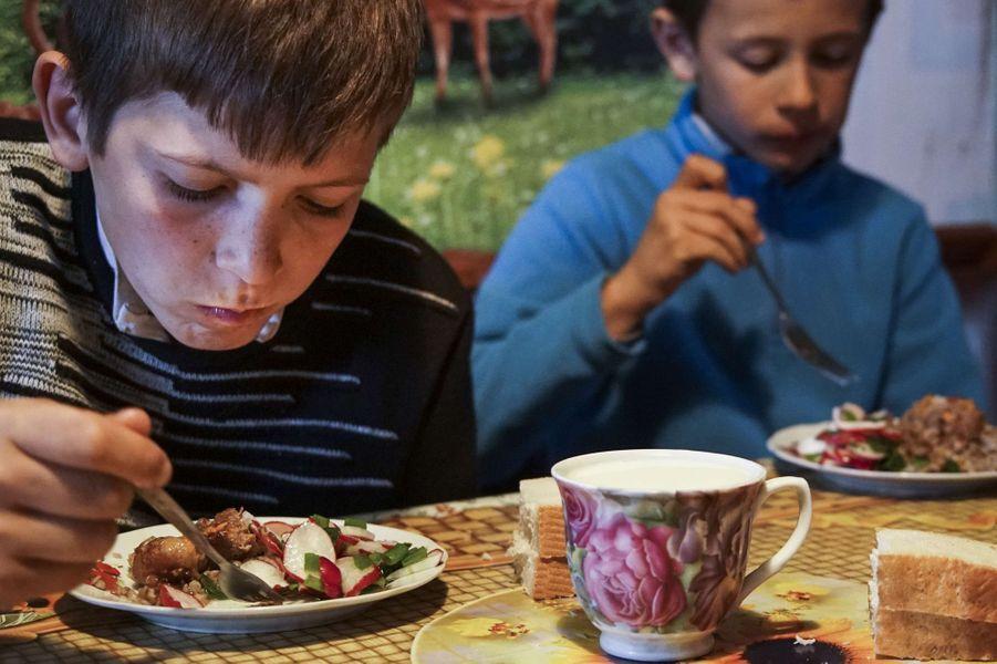 Bogdan et Kolya mangent chez eux à Zalishany (Ukraine). Bogdan souffre de problèmes de thyroïde, que sa mère pense liés à la catastrophe de Tc...