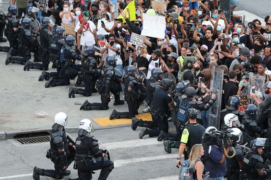 Des policiers mettent un genou à terre en signe de solidarité àAtlanta