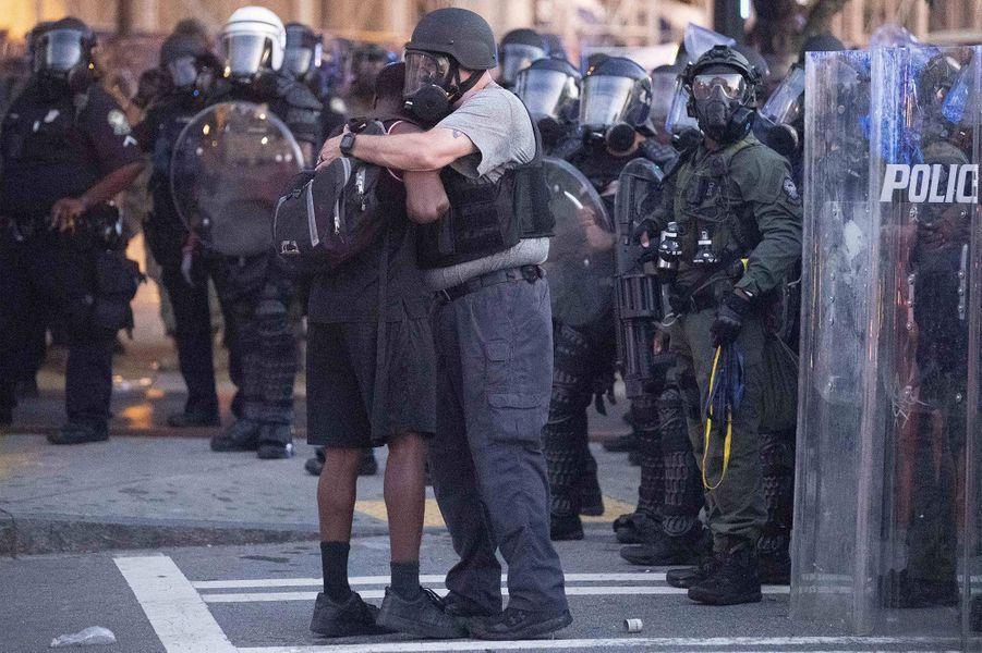 Un officier prend un manifestant dans ses bras àAtlanta