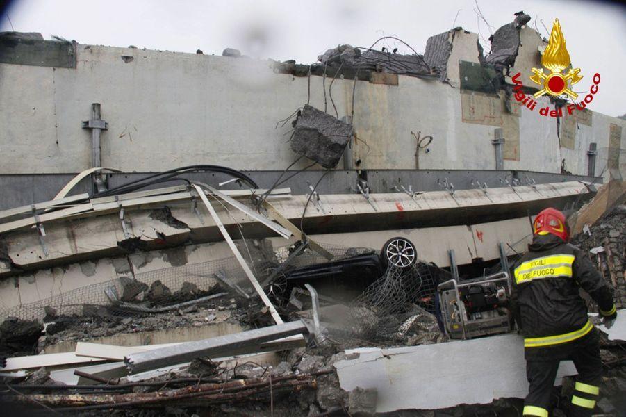 Une voiture écrasée sous le pont, sur un cliché diffusé par les pompiers, à Gênes, mardi.