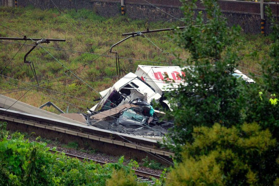 Un camion et une voiture tombés du pont Morandi, mardi à Gênes.