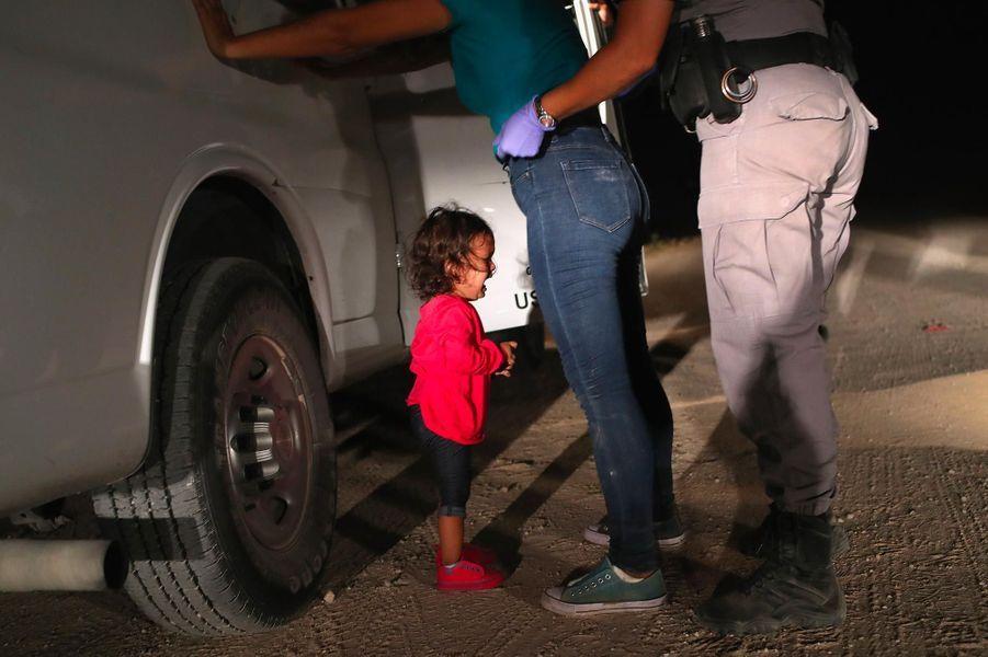 Une fillette hondurienne de deux ans fond en larmes alors que sa mère est fouillée par la police aux frontières à McAllen, au Texas, en juin 2018. L'image a valu au photographe John Moore de remporter le World Press Photo de l'image de l'année.