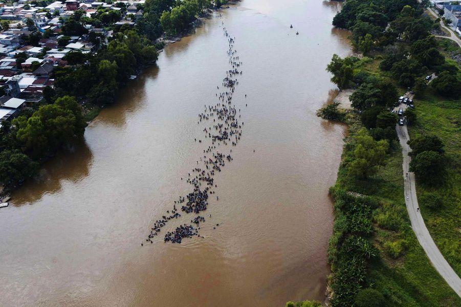Des dizaines de migrants traversent la rivièreSuchiate, entre le Guatemala et le Mexique, en octobre 2018.
