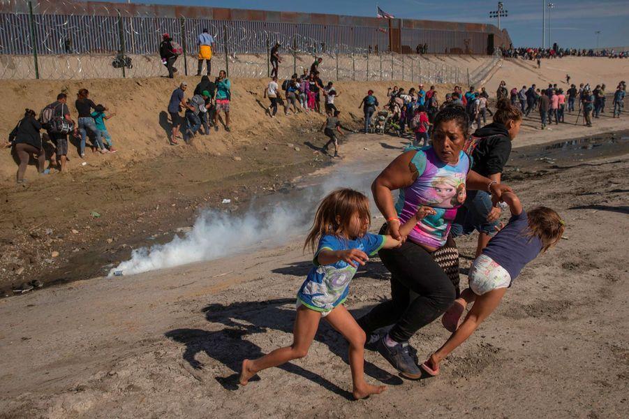 Maria Meza, 40 ans, fuit avec ses jumeaux de 5 ans Saira et Cheili alors que les autorités mexicaines tirent des gaz lacrymogènes, à Tijuana, en novembre 2018. L'image a valu au photographeKim Kyung-hoon de remporter le prix Pulitzer dans la catégorie «photo d'actualité».