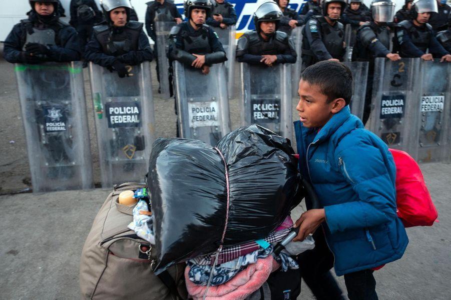 Un enfant, qui a marché parmi une des «caravanes» de migrants, avance devant les policiers mexicains à Tijuana, en janvier 2019.
