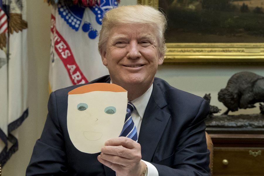 Donald Trump tenant un dessin le représentant, fait par un enfant, le 13 mars 2017.