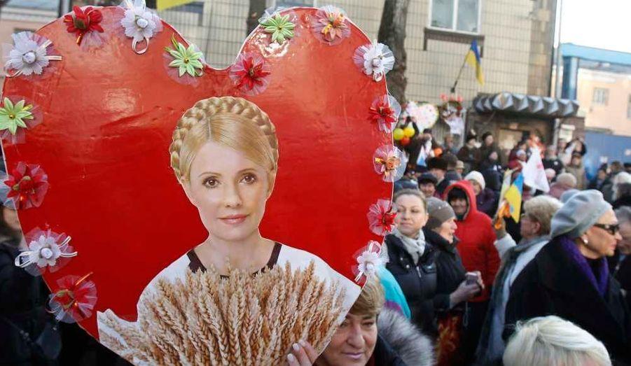 """Plus de 3000 partisans de l'ex-Premier ministre ukrainien Ioulia Timochenko se sont rassemblés dimanche devant la prison de Loukianivska, à Kiev, à l'occasion de son 51e anniversaire. Les manifestants ont déposé des fleurs et accroché des messages rédigés à la main sur des cartes en forme de coeur, sur la façade du centre pénitentiaire. L'""""égérie de la révolution orange"""" a été condamnée le mois dernier à sept ans d'emprisonnement pour abus de pouvoir, pour avoir ordonné en 2009 la conclusion d'un accord gazier avec la Russie, désormais jugé contraire aux intérêts de l'Etat. L'Ukrainienne aux tresses blondes, qui a dénoncé un procès politique conduit par le président Viktor Ianoukovitch, a en outre été inculpée d'évasion fiscale et de vol et recel de devises étrangères ce mois-ci."""