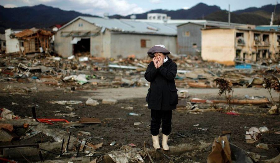 Quand tout est à refaire... Une femme, au téléphone, regarde sa maison détruite par le séisme et le tsunami dans la ville Kessenuma, dans la préfecture de Miyagi.